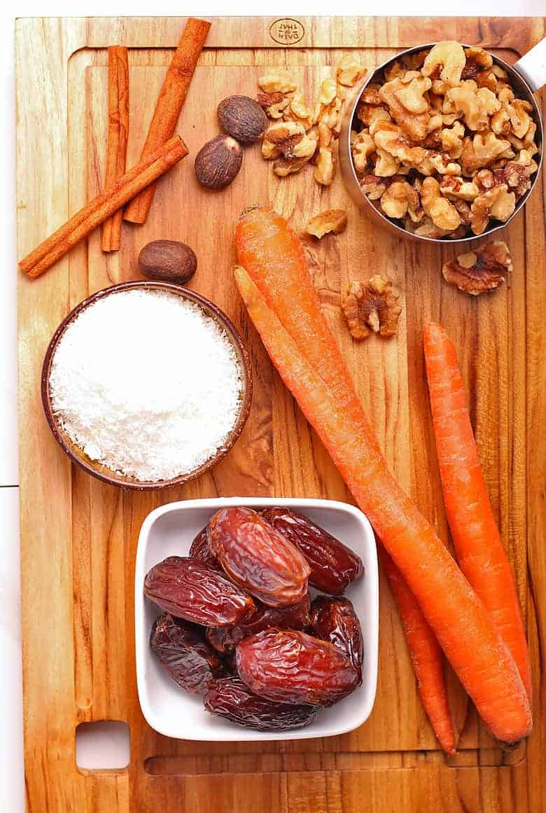 Dates, carrots, walnuts, and shredded coconut on a cutting board