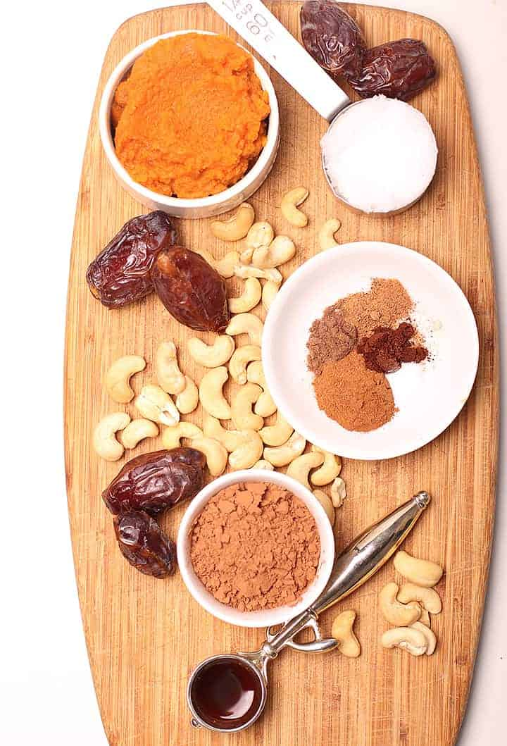 spices, cashews, dates, and pumpkin puree on a wooden platter
