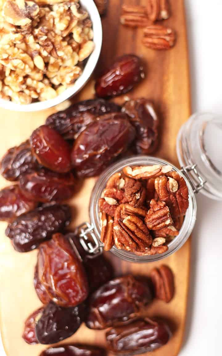 Dates, pecans, and walnuts on wooden platter
