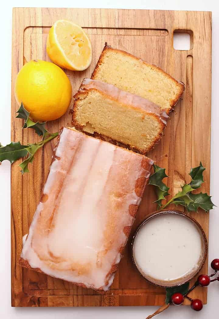 Vegan Pound Cake on a cutting board with holly and lemons