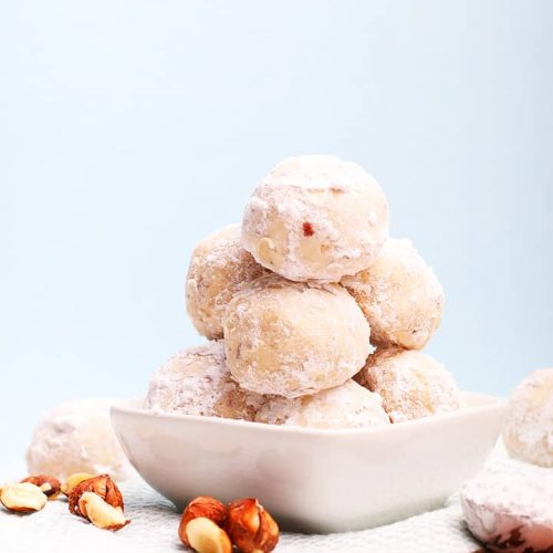 Stack of snowball cookies in a small white bowl