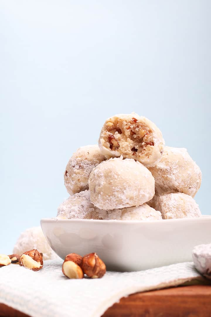 Stack of snowball cookies with a bite.