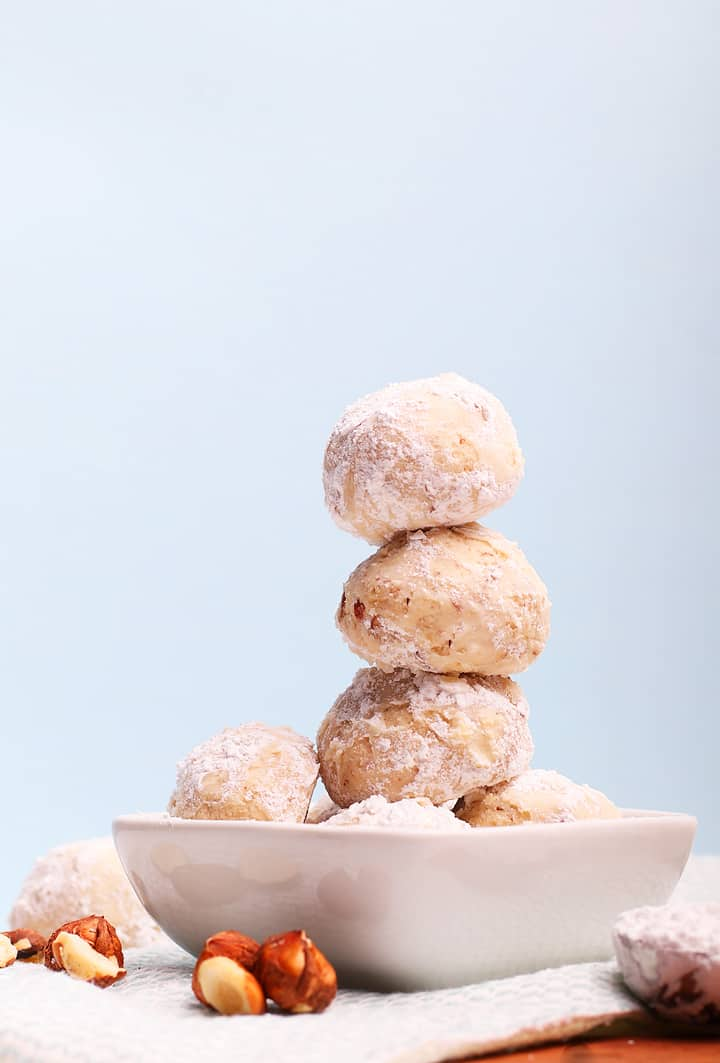 Three snowball cookies stacked on top of one another in a white bowl.