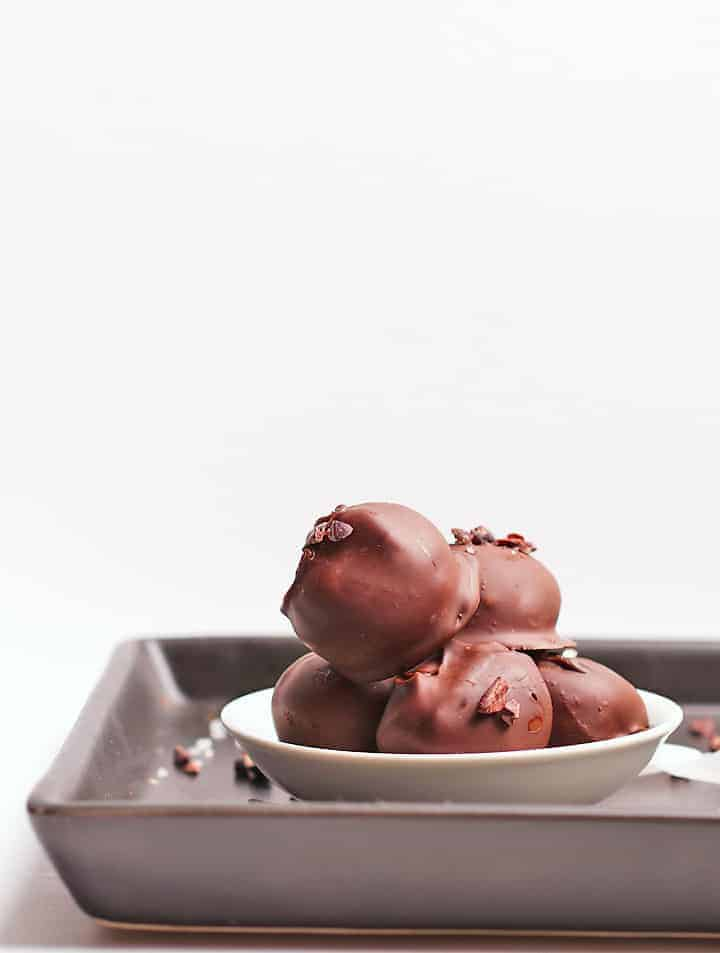 Vegan Chocolate Truffles in a white bowl on a black platter.