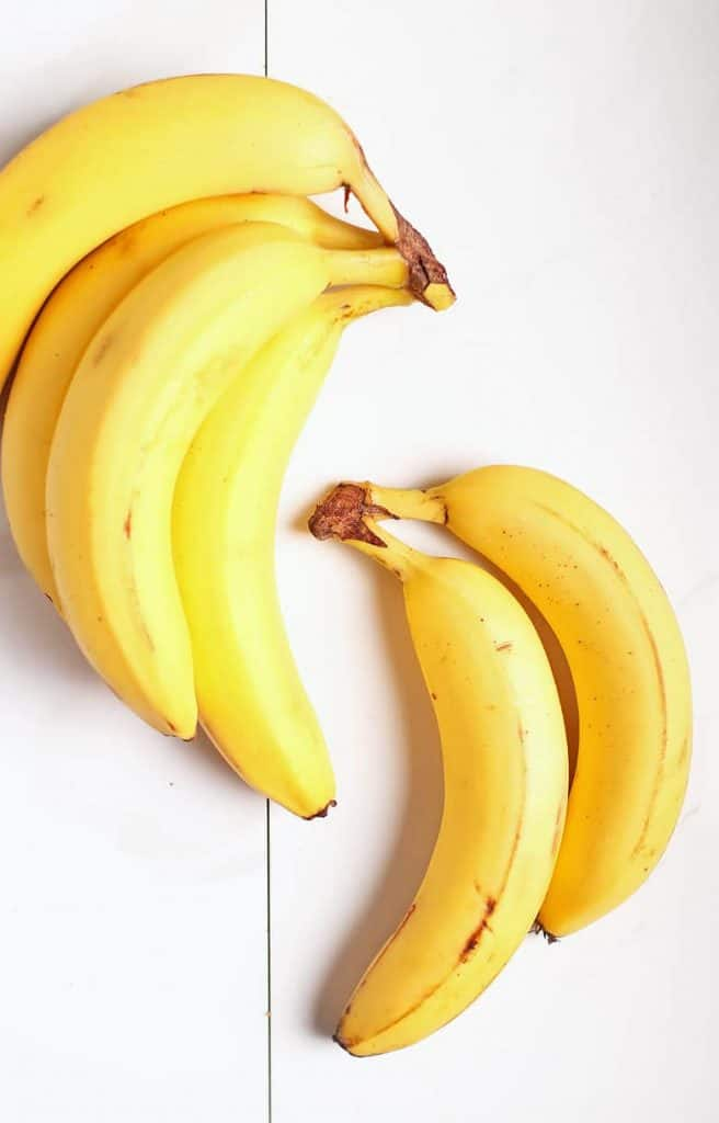 Two bunches of bananas on white background
