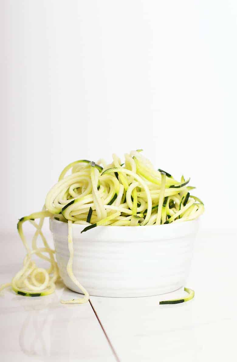 Bowl of zucchini noodles with a white background