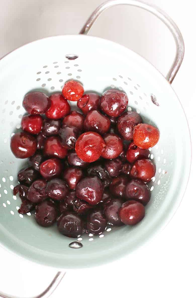Frozen cherries in a blue colander