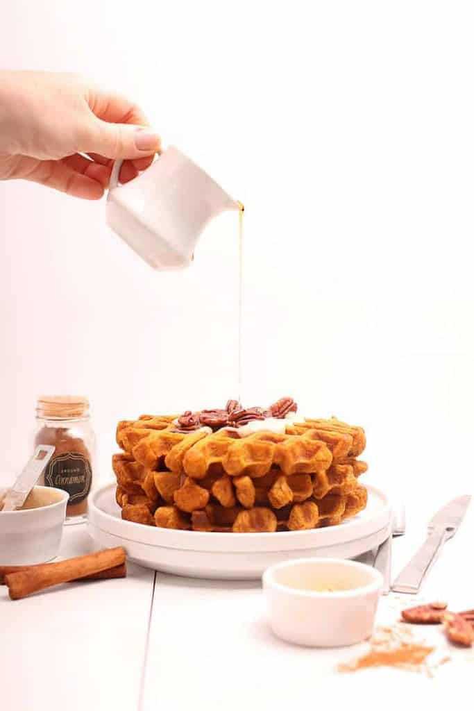 Stack of pumpkin waffles with maple syrup