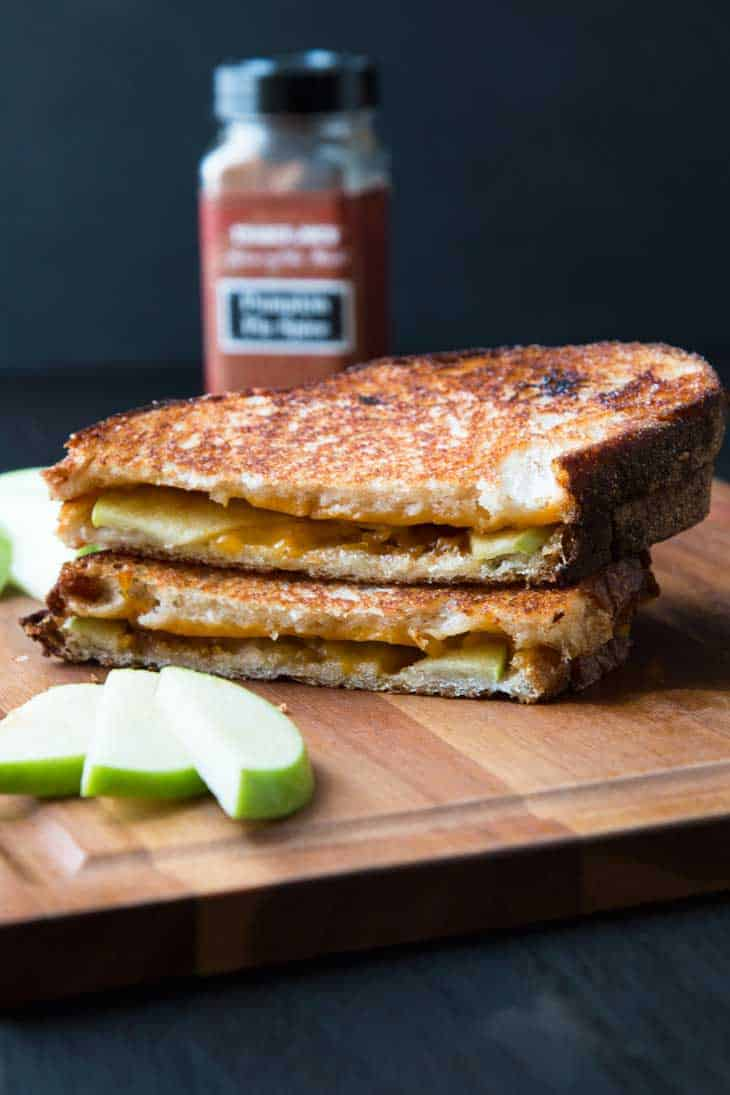 Vegan Pumpkin Grilled Cheese on a cutting board with apple slices.