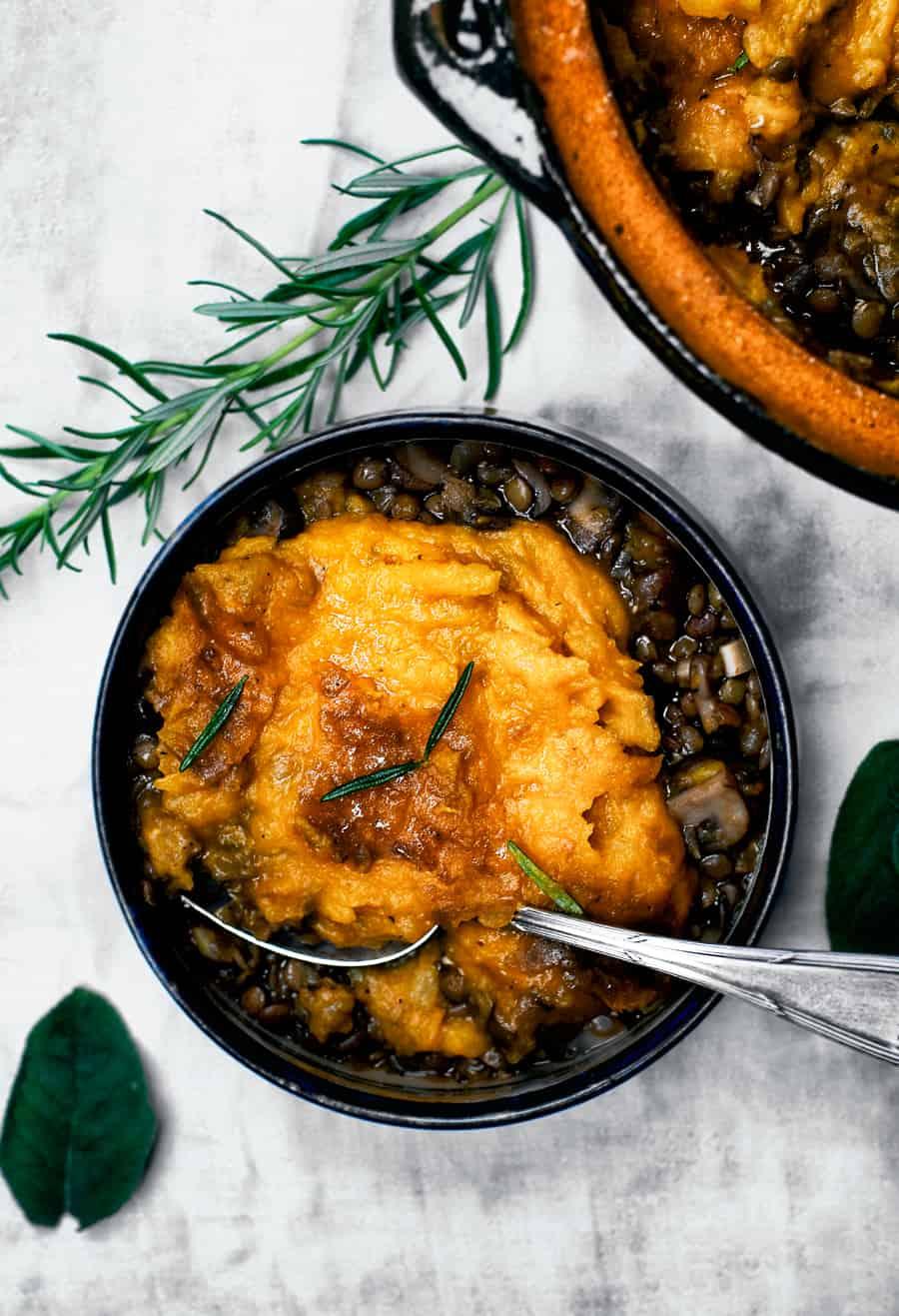 Pumpkin Mushroom Shepherds Pie in a black bowl with rosemary.