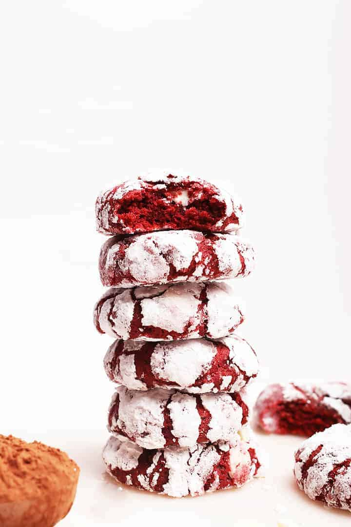 Stack of red velvet crinkle cookies with a bite taken out.