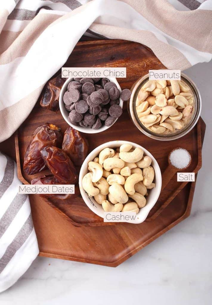 Cashews, peanuts, chocolate chops, and Medjool dates on a wooden platter