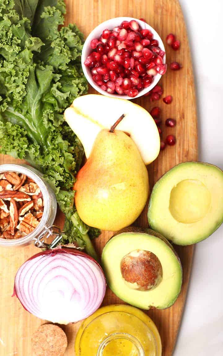 Pears, avocados, onions, and kale on cutting board