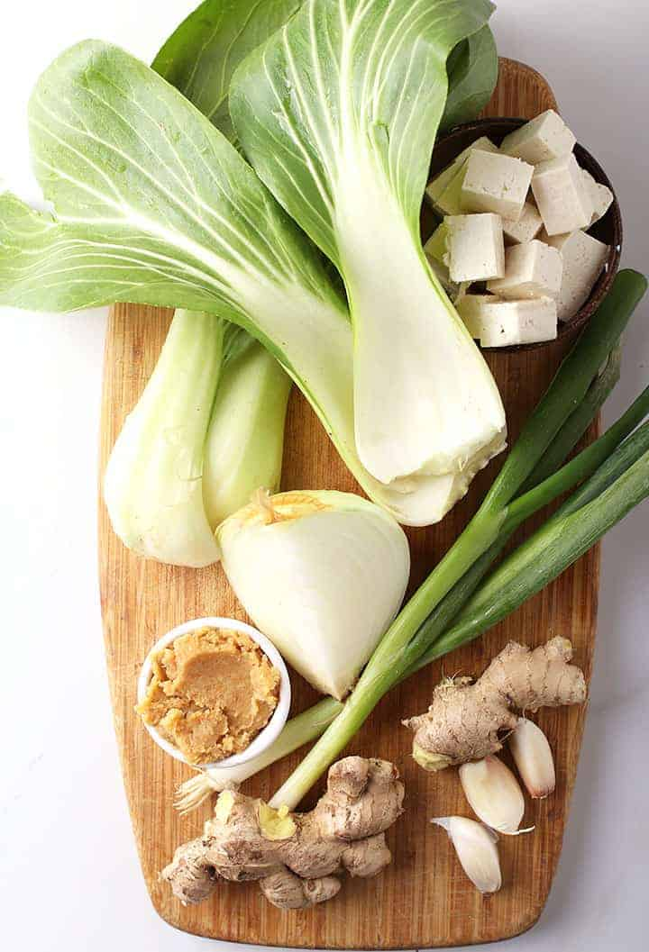 Ginger, garlic, miso paste, and onions on cutting board