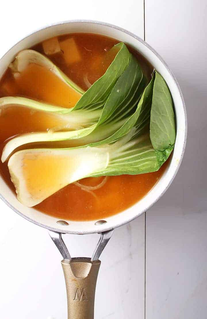 Bok choy in soup pot with broth
