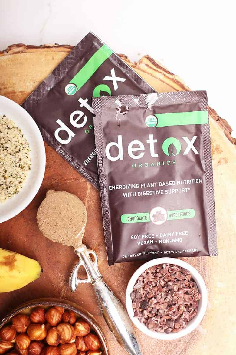Detox Organic packets and ingredients for Chocolate Smoothie Bowls on a wooden platter.