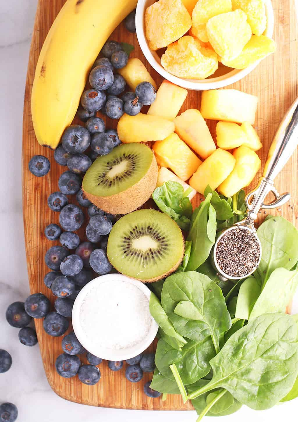 Blueberries, kiwi, banana, and spinach on a cutting board
