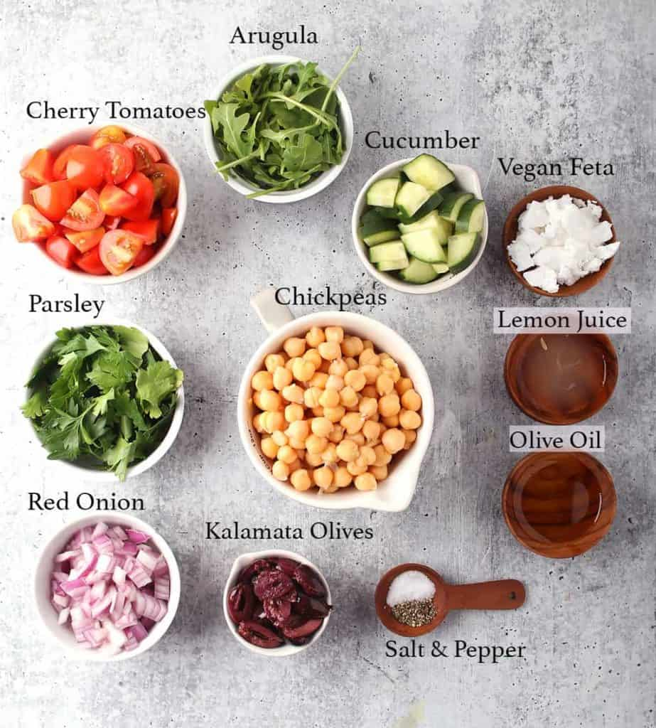 Ingredients for Greek salad measured out and placed on a concrete countertop