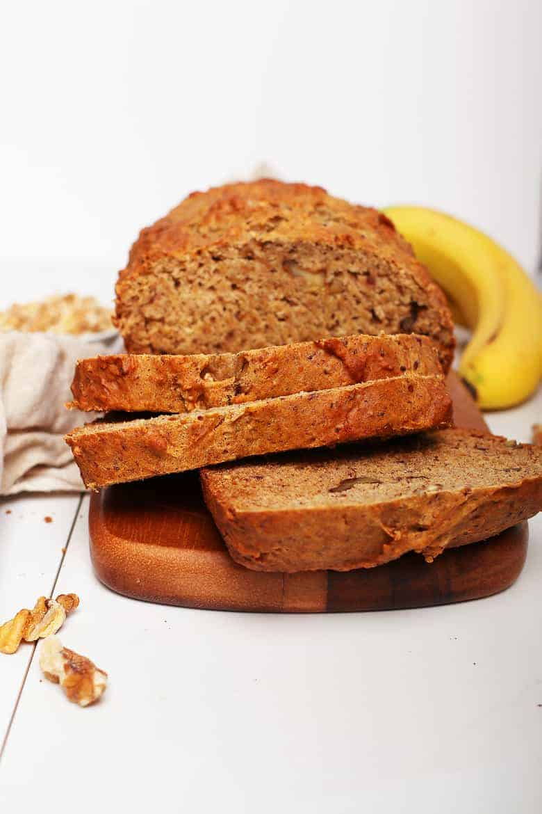 Vegan banana bread cut into slices on a cutting board.