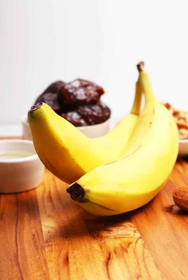 Two bananas on a wooden cutting board