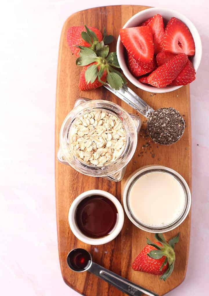 Oats, milk, and sliced strawberries on cutting board