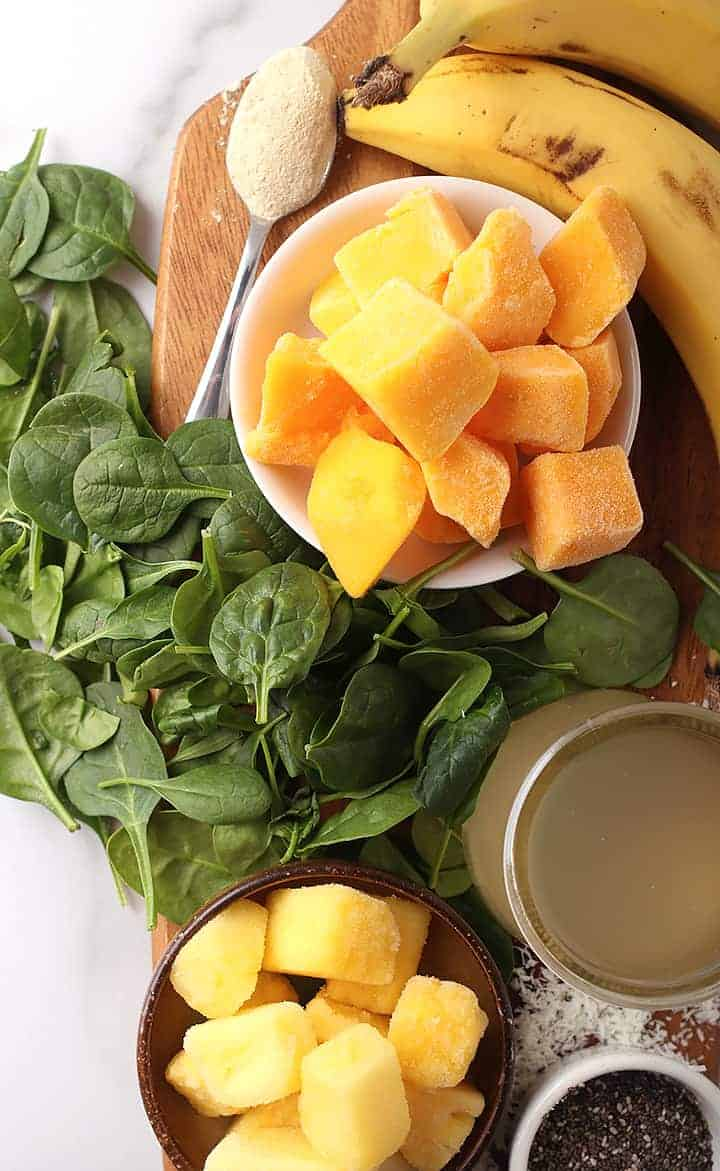 Spinach, mango, banana, and pineapple on wooden platter