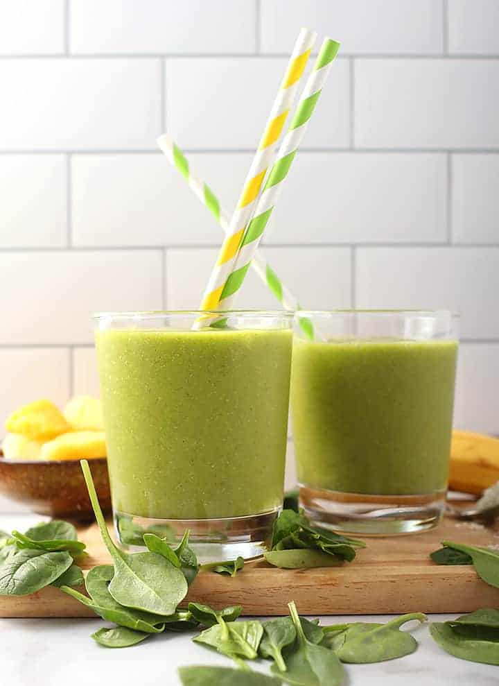 Two vegan green smoothie with striped straws