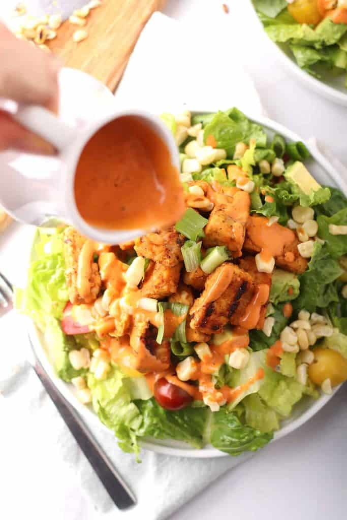 Chipotle ranch dressing pour onto a salad
