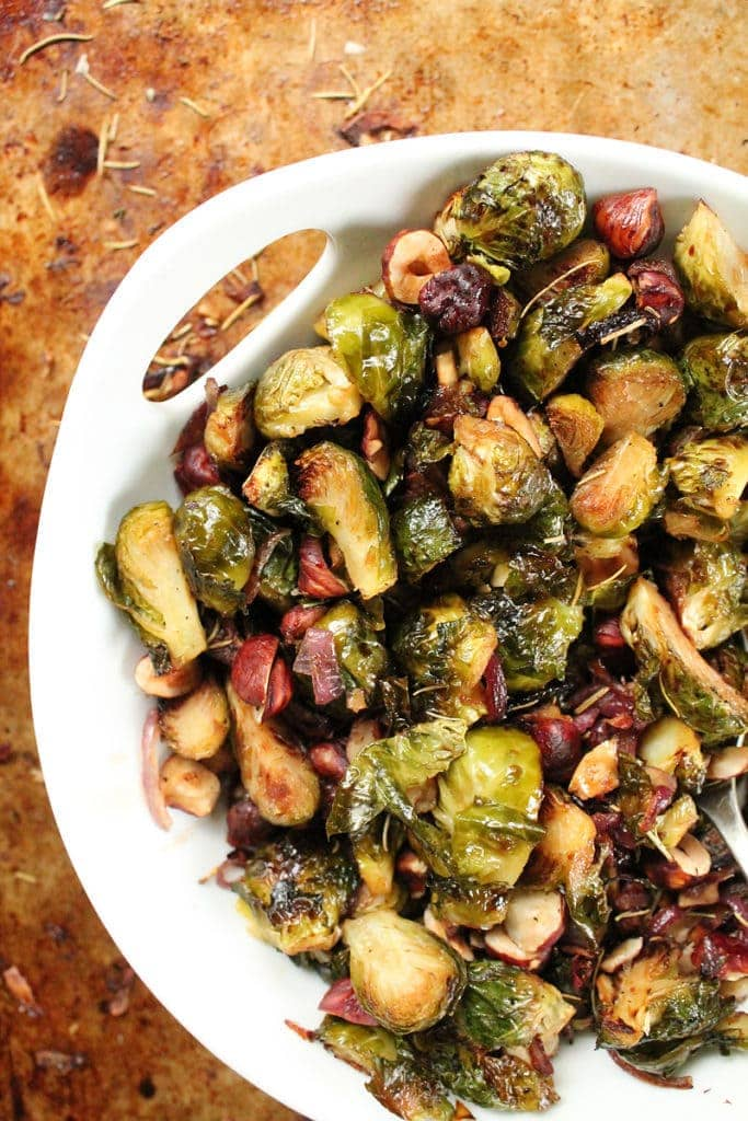 Balsamic Brussels Sprouts with Hazelnuts and Onions in a white bowl.