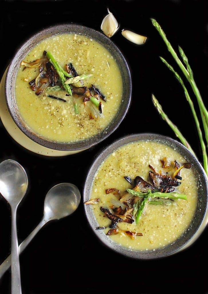 Two bowls of cream of asparagus soup with caramelized onions.