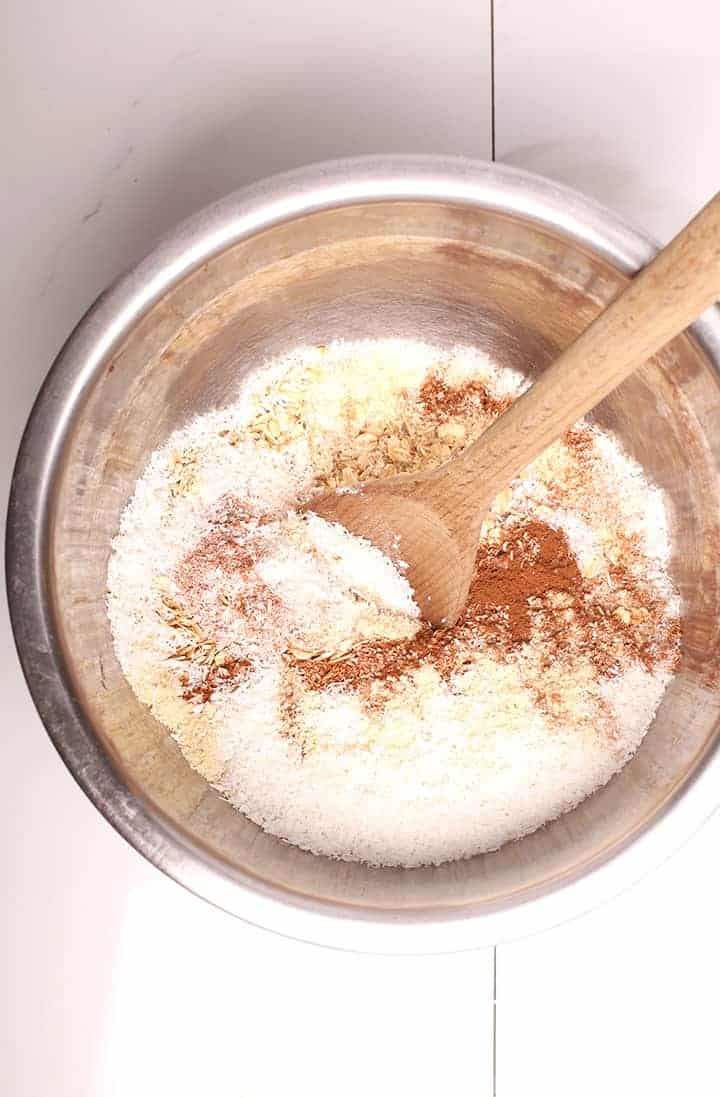 Oats, coconut, and spices in a mixing bowl