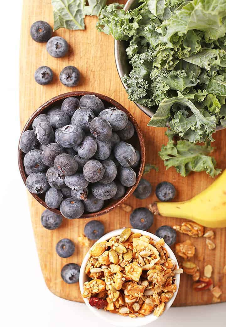 Blueberries and kale on cutting board