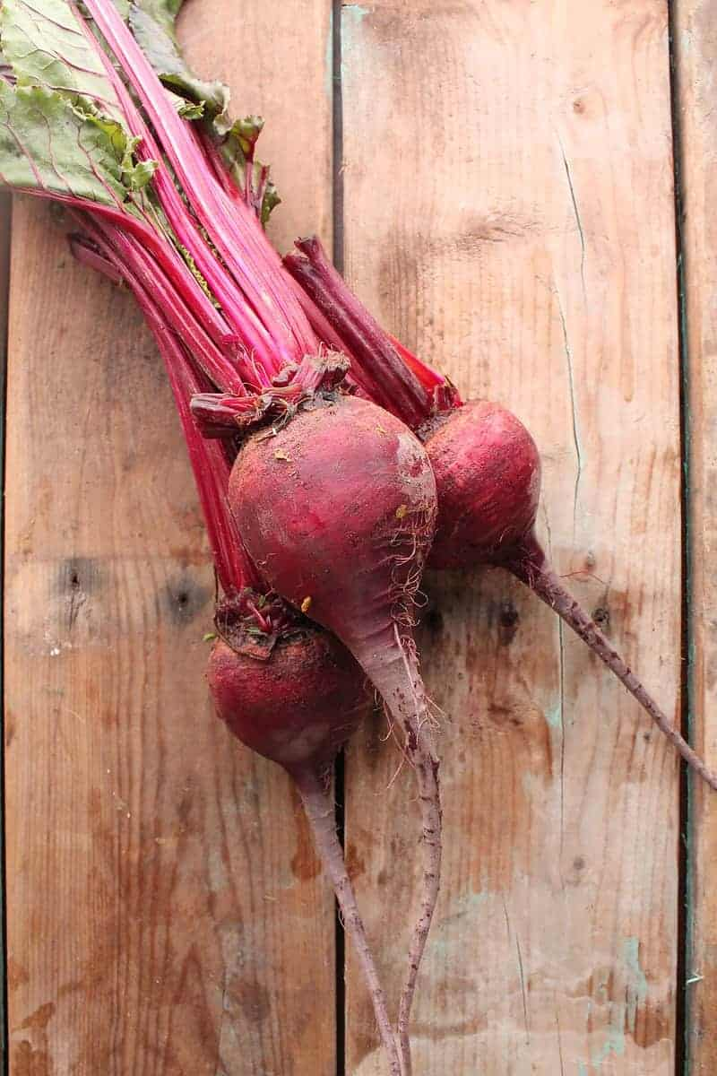Three beets on wooden backdrop