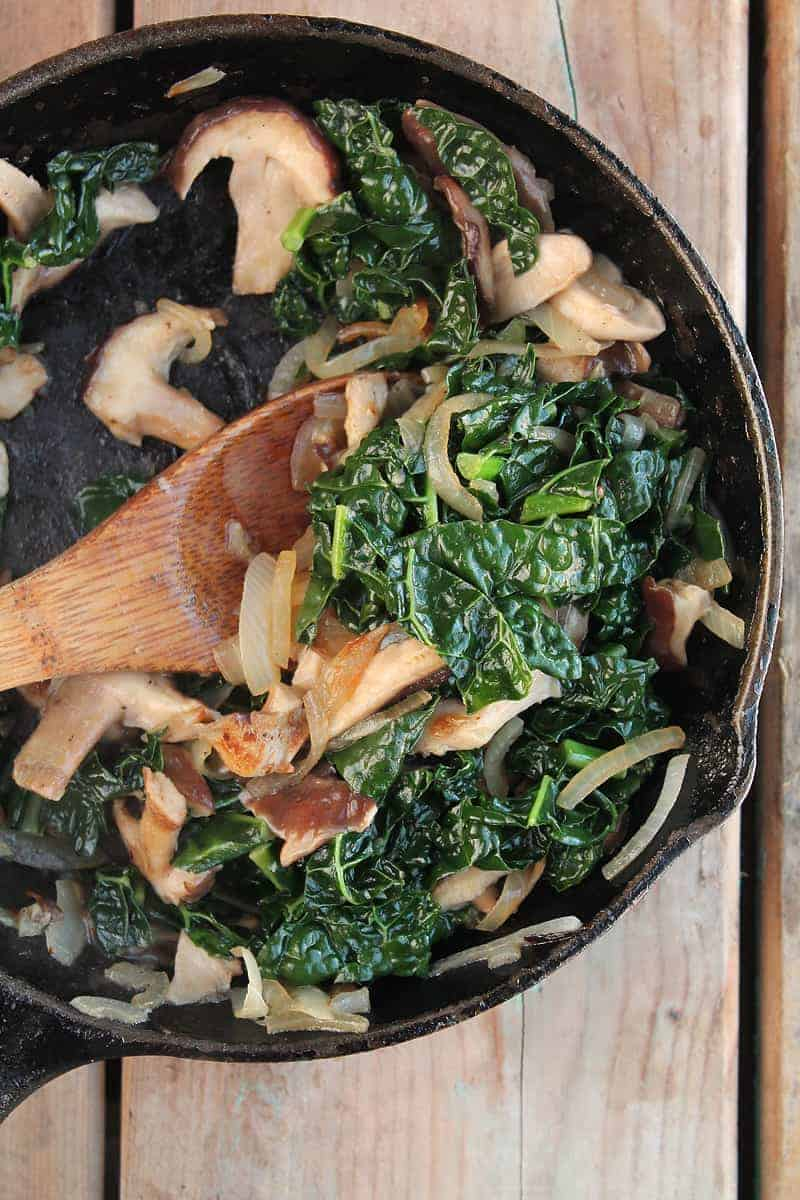 Mushrooms and kale in a cast iron skillet
