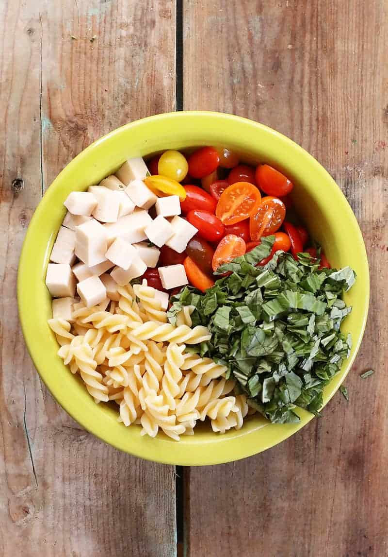 Tomatoes, pasta, basil, and cheese in bowl