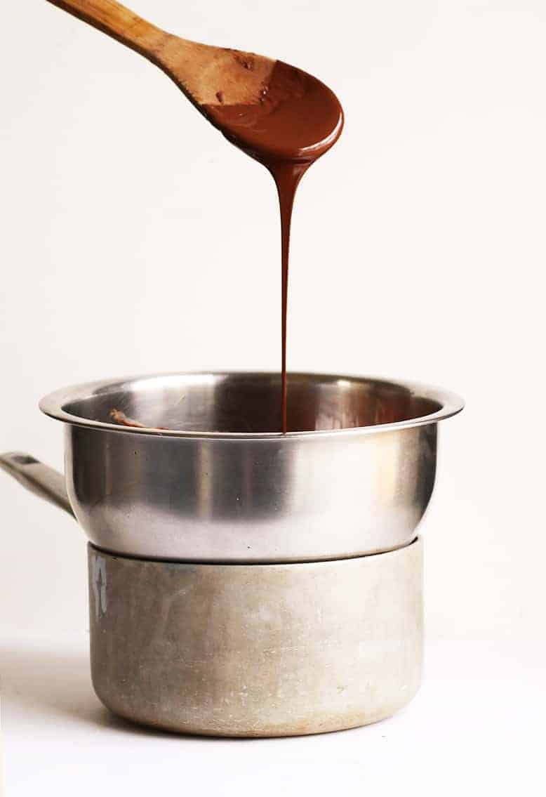 Melted chocolate dripping off wooden spoon into a double boiler.