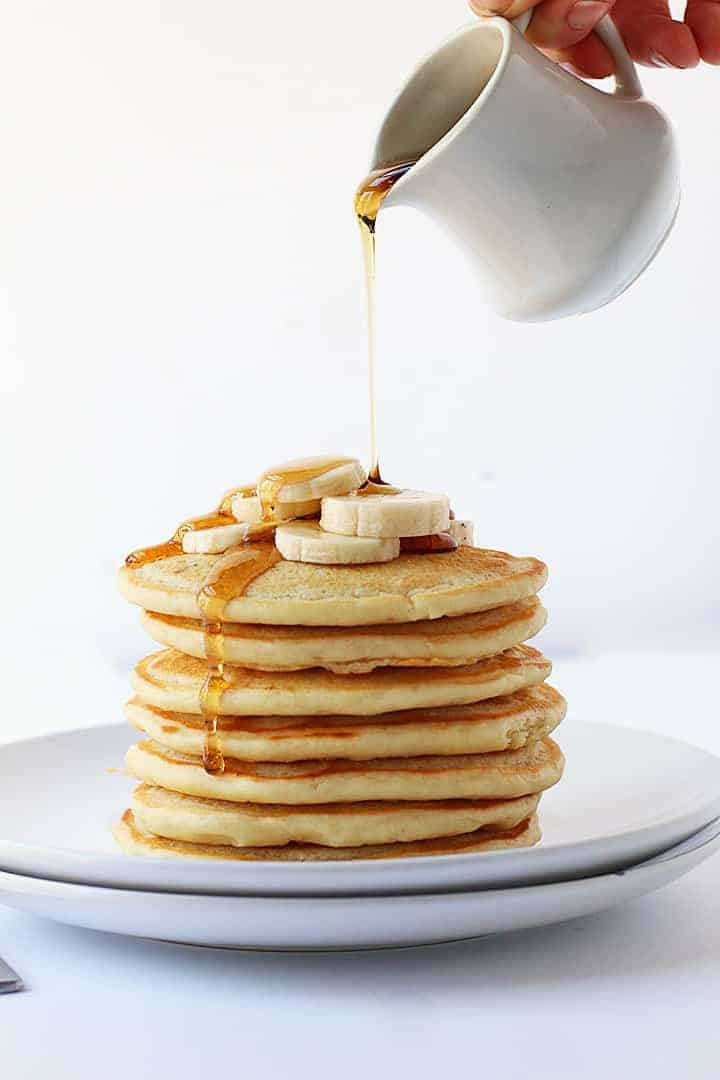 Stack of vegan pancakes topped with maple syrup
