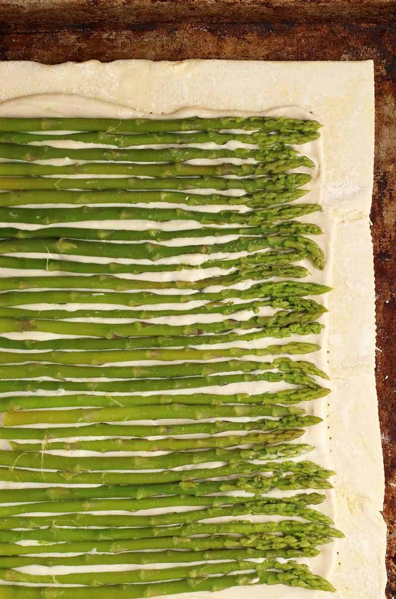 Raw asparagus covering a raw puff pastry