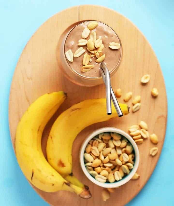 Chocolate smoothie on a wooden board with bananas and peanuts