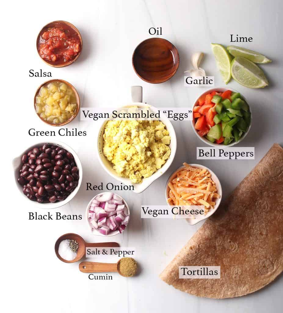 Ingredients for vegan breakfast burrito measured out on a marble countertop