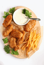 Finished recipe on a wooden platter with fries and tartar sauce