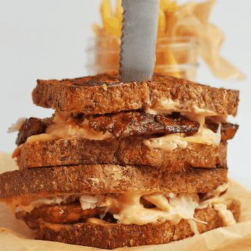 Finished sandwich on a wooden board with a steak knife