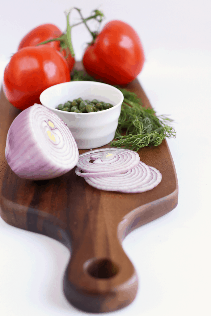 Onions, tomatoes, and herbs on cutting board