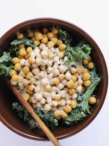 Finished salad in a large salad bowl with a wooden spoon