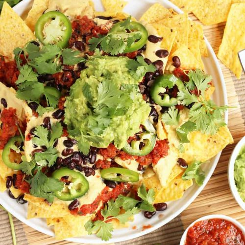Finished plate of vegan nachos with fresh guacamole