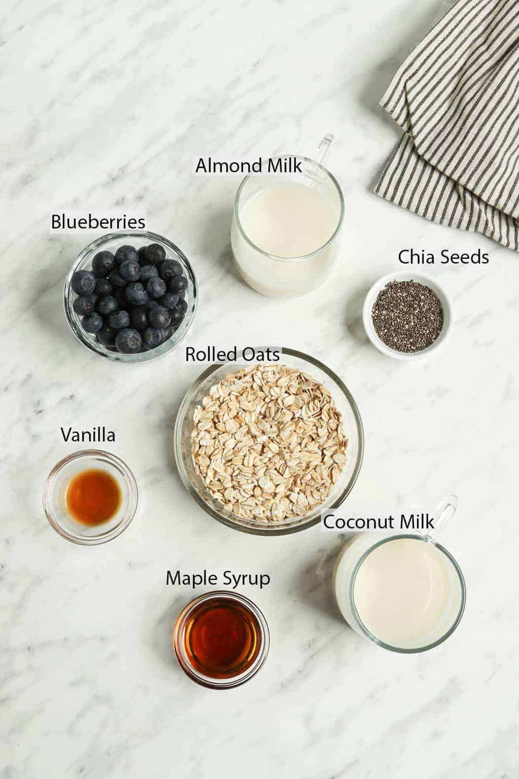 Ingredients for overnight oats measured out and placed on a marble countertop.