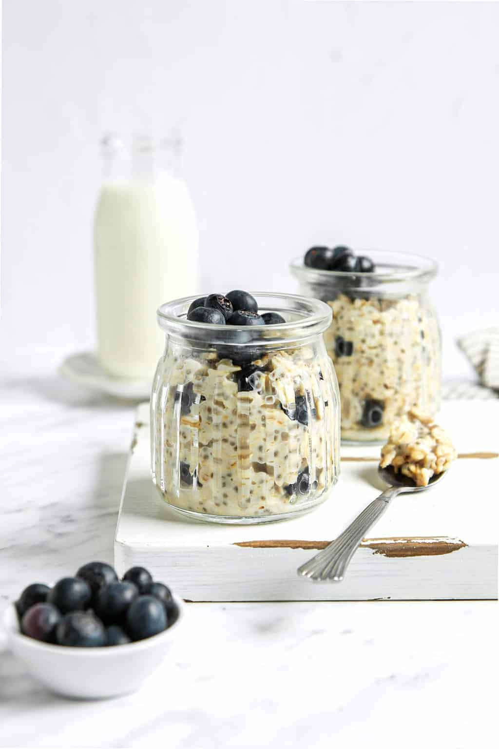 Two jars of overnight oats with blueberries on a white wooden board.