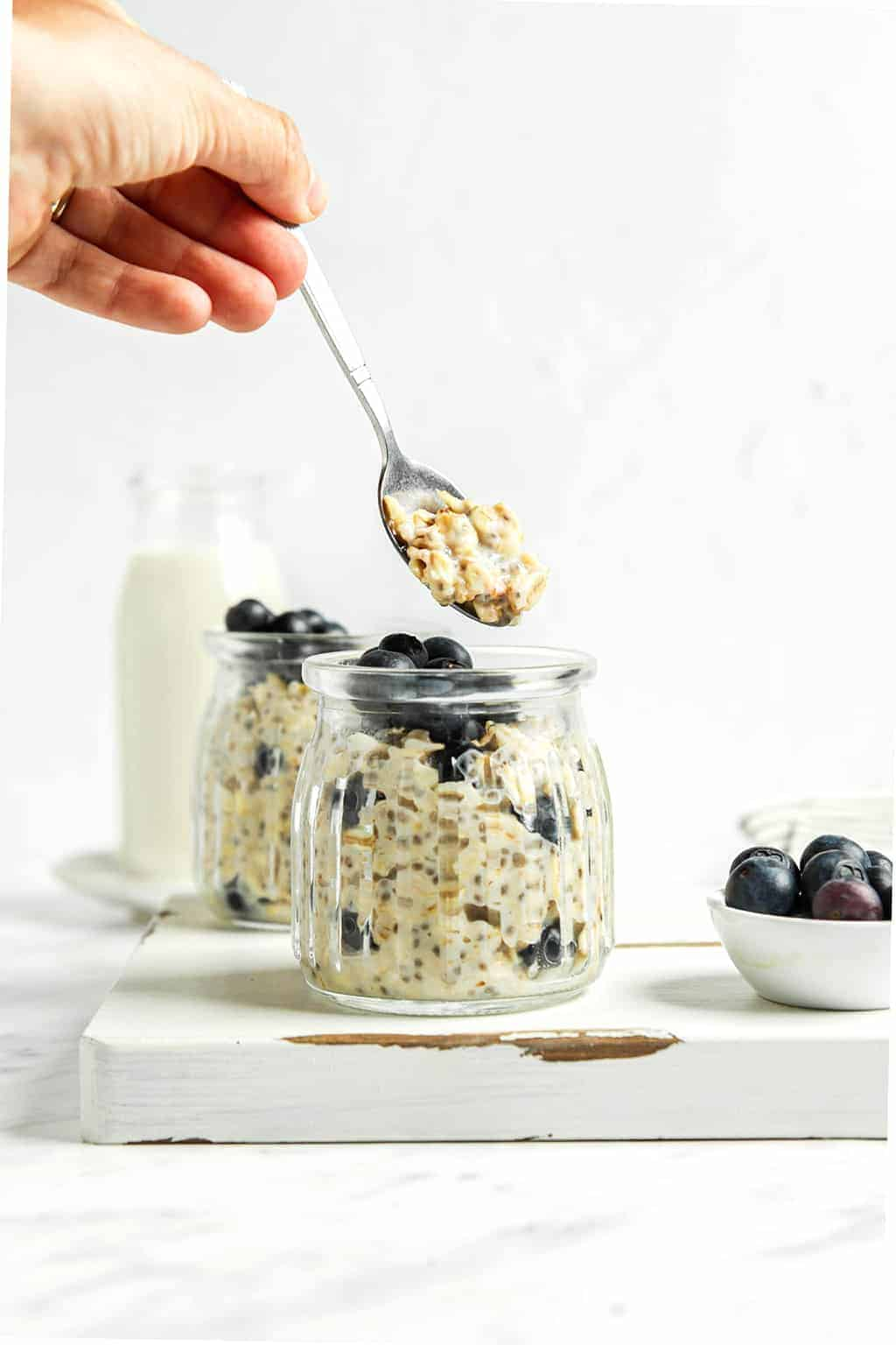 Hand holding a spoonful of overnight oats over finished oats.