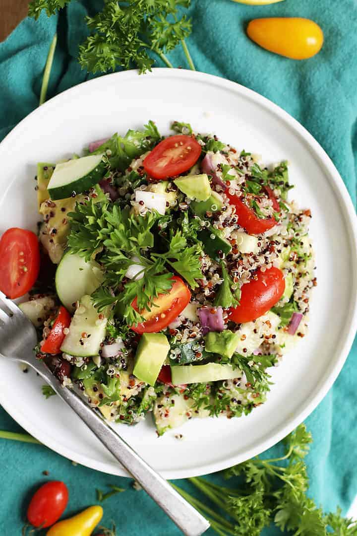 Mediterranean Quinoa Salad on a white plate with a fork