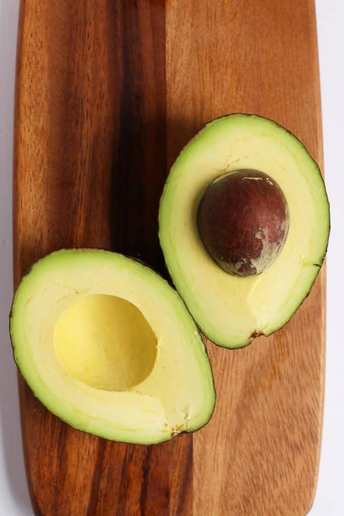 An avocado cut in half on a wooden board